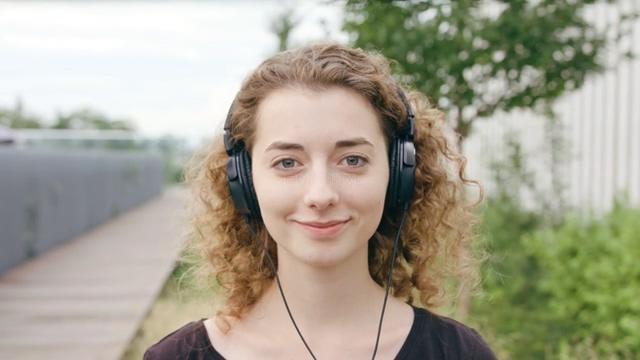 戴上耳机听音乐微笑的卷发美女