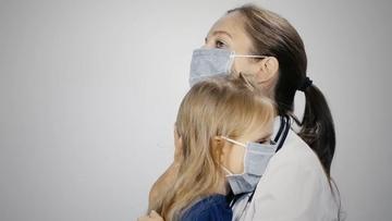 戴口罩的医生安慰小女孩