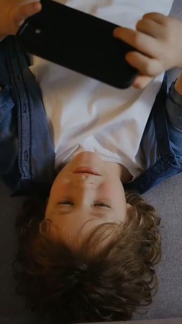玩手机游戏的小胖男孩