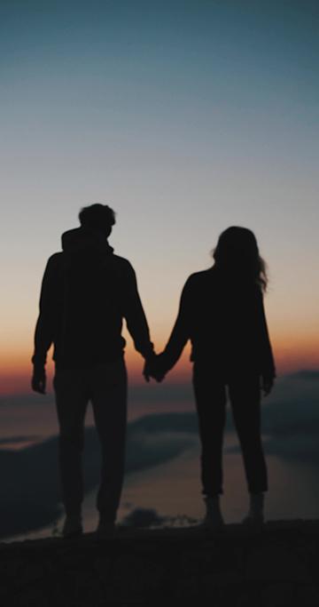 山顶上牵手的情侣剪影