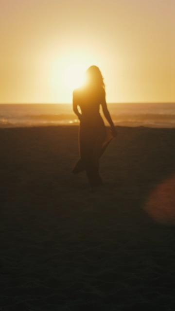 在日落时在沙滩上散步的女人的剪影