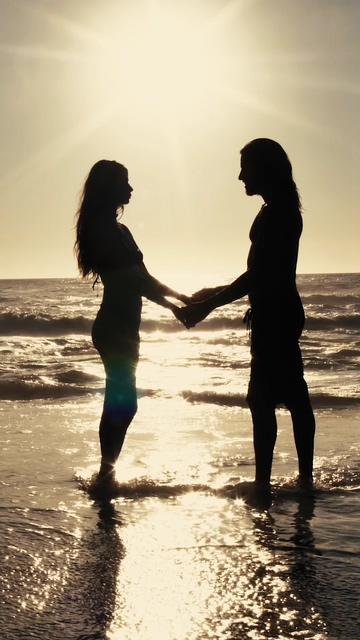 日落时分在海滩上的情侣剪影