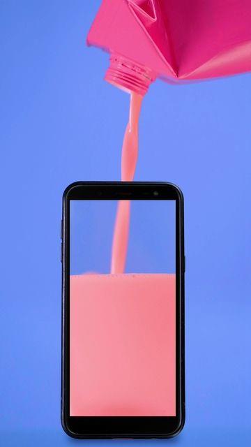 往手机里倒入粉色的果汁液体视频
