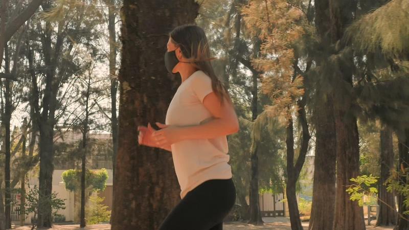 侧面戴口罩跑步的丰满女人视频素材