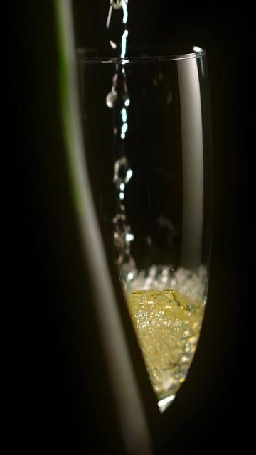 香槟倒入玻璃酒杯在深色背景上