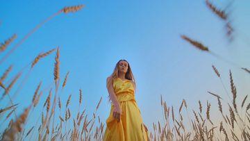 4K穿金色裙子走在麦田里的美女