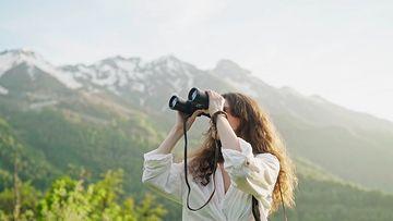 在山谷里看望眼镜的卷发女孩视频素材