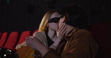 在电影院里看电影亲吻的情侣