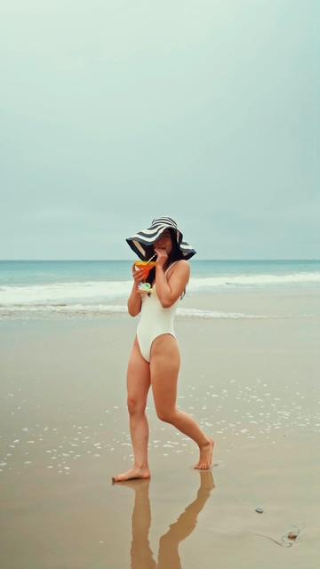 在海边漫步喝果汁的女孩竖屏视频
