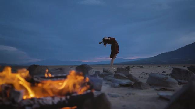 燃烧的火堆后面有一个女人在放空自己视频