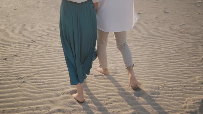 情侣赤脚走在沙滩上视频素材