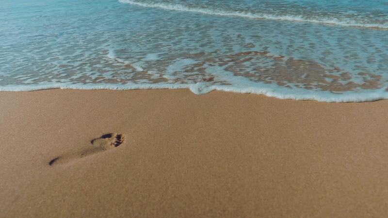 4K海浪淹没沙滩上的脚印视频素材