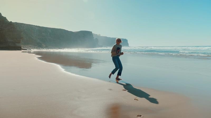 4K拿着相机在沙滩上奔跑美女背影视频素材