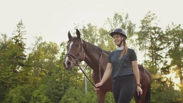 4K牵着马在走路的女人微笑视频素材