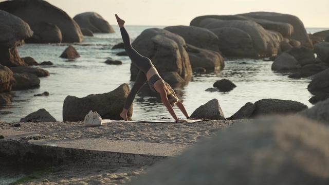 石头前景虚化在做瑜伽的人视频素材