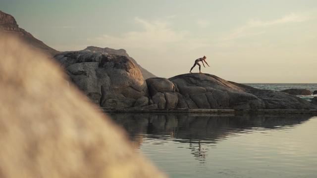 透过石头看到远处在做瑜伽的人视频素材