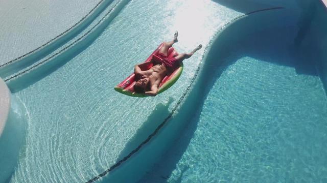4K高端生活在用泳池上漂浮享受生活的男人视频素材