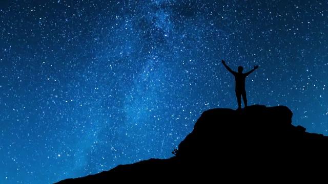 星空下站在山顶上挥手的人剪影视频