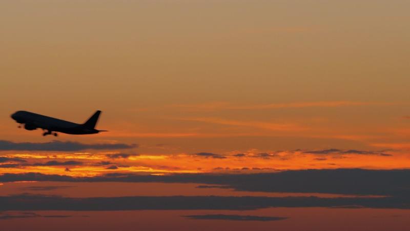 4K火烧云前飞机飞过剪影视频